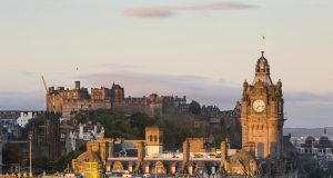 Edinburgh Castle and the Balmoral Hotel clocktower at sunrise