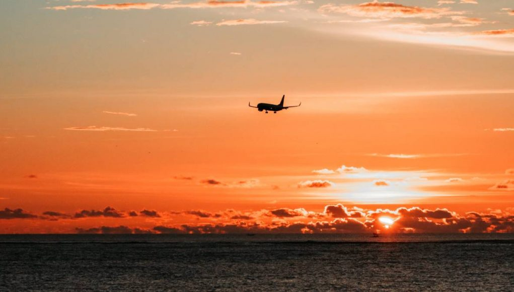 airplane flying off in the sunset