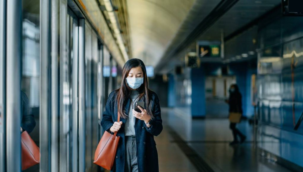 Asian woman with protective face mask using smartphone while walking on the subway platform