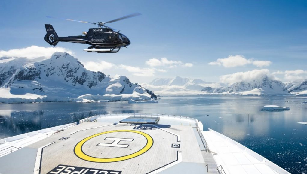 helicopter landing on the front of a luxury cruise ship