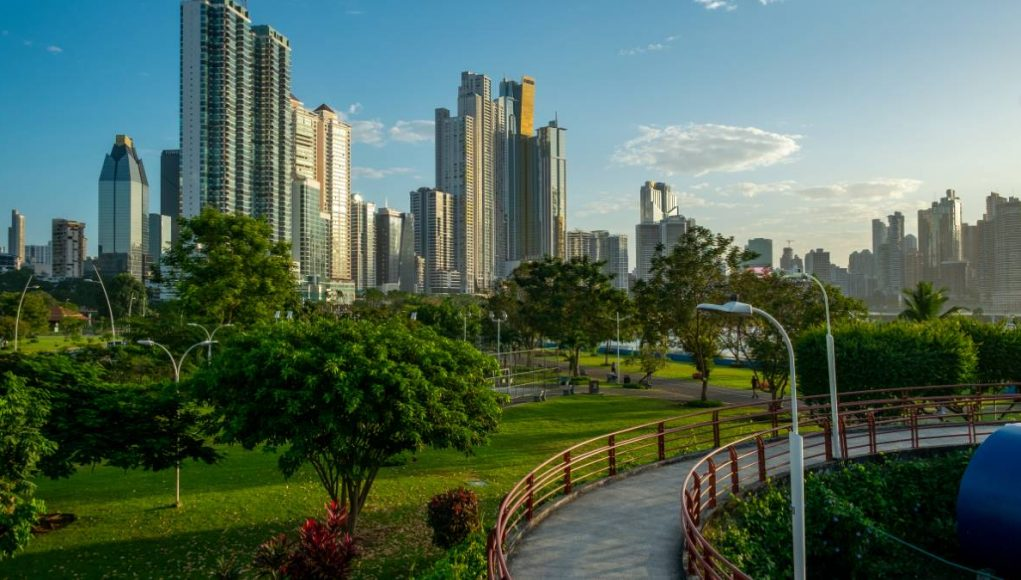 Pedestrian overpassin the Cinta Costera/ walkway with city skyline background and palm trees , Panama City , Central America