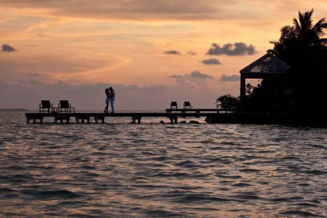 couple on a dock at sunset in Belize