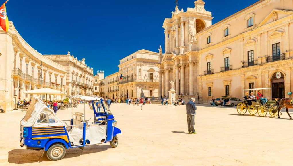 View of The Cathedral of Syracuse and the central square (Piazza Duomo) with walking people